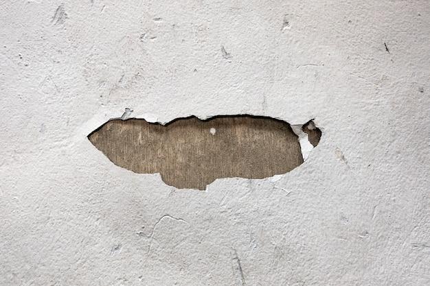 Pęknięta biała ściana z dziurą