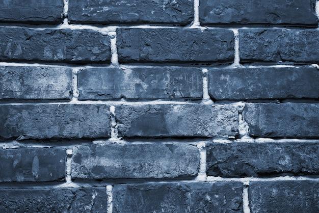 Pęknięta i teksturowana niebieska ściana, ściana z cegieł. kolor koncepcji roku 2020.