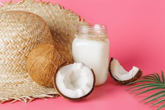Pęknięte mleko kokosowe i kokosowe w szkle na jasnym różu