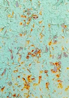Pęknięty i obieranie farby w kolorze zielonym na stali z zardzewiałą teksturą i tłem