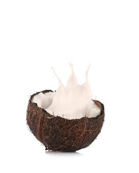 Pęknięty kokos z plamami mleka na białej przestrzeni