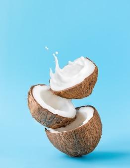 Pęknięty kokos z plamami mleka na niebieskim tle.