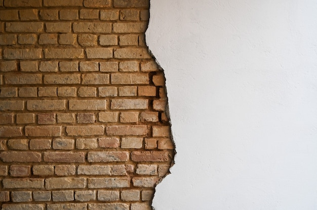 Pęknięty mur z cegły i szpachlówka.