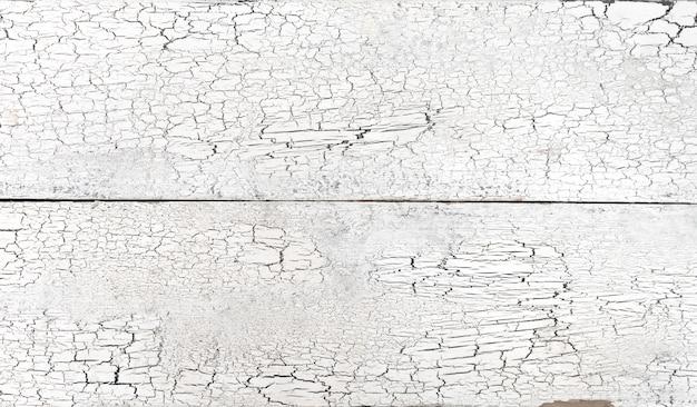 Pęknięty starej białej farby na drewnianych deskach z powrotem pęknięty starej białej farby na drewnianych deskach tło grunge wyblakły deska grunge wyblakły deska