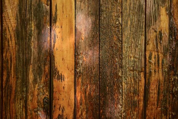 Pęknięty stary drewniany tło z brązowych pionowych desek.