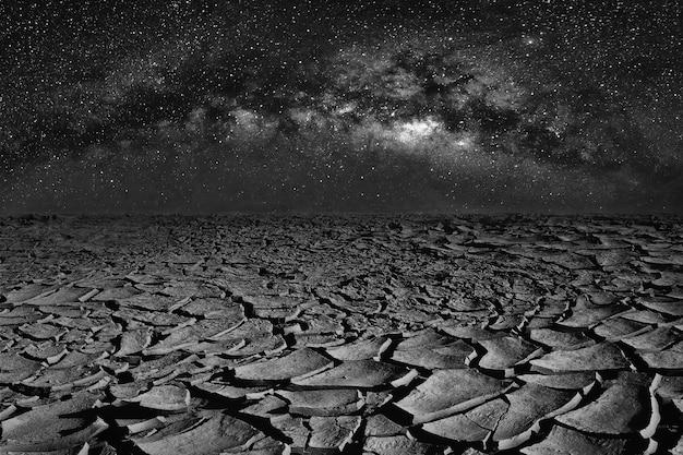 Pęknięty suchy ląd i wszechświat przestrzeni galaktyki drogi mlecznej na nocnym niebie.