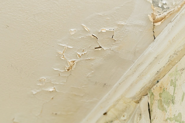 Pęknięty tynk na suficie po wycieku wody z górnego piętra domu mieszkalnego