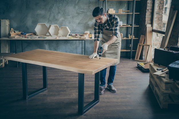 Pełen ciała przystojny, ostrożny facet, montujący ręcznie robiony stół z płyt, wykonujący czynności wykończeniowe przed sprzedażą własnej strony internetowej z branży drewnianej w warsztacie stolarskim wewnątrz