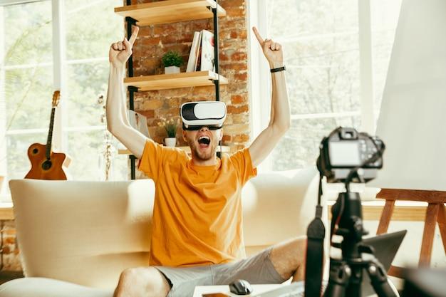 Pełen emocji. kaukaski bloger z profesjonalnym aparatem nagrywającym w domu przegląd wideo okularów vr. blogowanie, videoblog, vlogowanie. mężczyzna korzystający z zestawu słuchawkowego wirtualnej rzeczywistości podczas przesyłania strumieniowego na żywo.