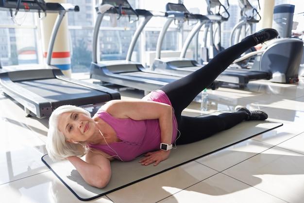 Pełen energii. rozbawiona piękna starsza kobieta, słuchając muzyki podczas ćwiczeń na dywanie w siłowni.
