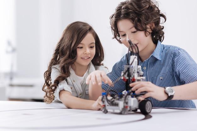 Pełen entuzjazmu. urocze, uważne zaangażowane dzieci siedzą w szkole i tworzą robota, jednocześnie wyrażając radość