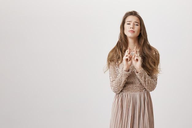 Pełen nadziei błagająca kobieta trzymaj kciuki, załóż suknię wieczorową