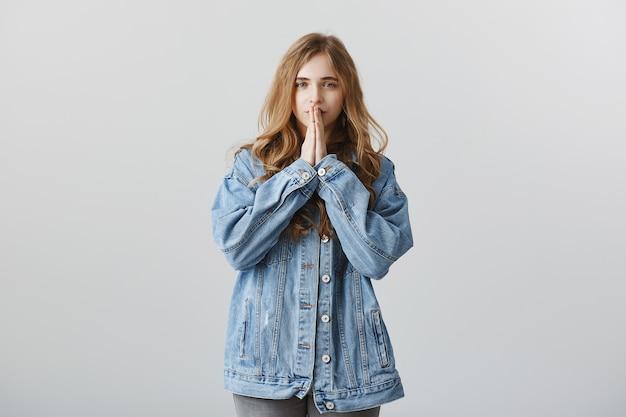 Pełen nadziei blondyn w dżinsowej kurtce wypowiadający życzenie, błagalnie trzymając się za ręce, modląc się