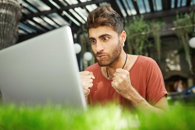 Pełen nadziei i spięty przystojny programista zaciska pięści i patrzy z niecierpliwością na ekran laptopa testujący program