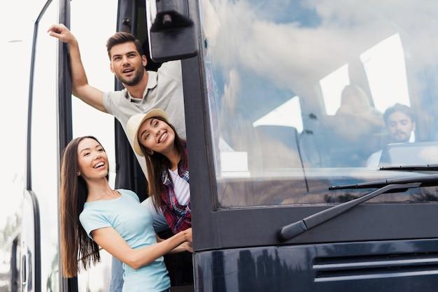 Pełen nadziei młodzi ludzie przy drzwiach autokaru podróżnego.