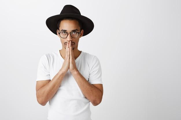 Pełen nadziei przystojny afroamerykanin młody mężczyzna trzyma się za ręce w modlitwie, błaganiu lub proszeniu