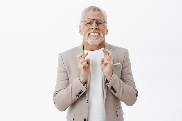 Pełen nadziei starszy mężczyzna w garniturze ze skrzyżowanymi palcami powodzenia, życząc sobie