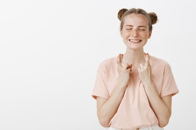 Pełen nadziei uśmiechnięta nastolatka pozuje na białej ścianie