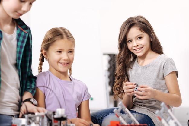 Pełen pozytywnych emocji. słodkie, optymistyczne, śliczne dzieciaki siedzą w laboratorium robotyki i testują urządzenia cybernetyczne podczas lekcji przedmiotów ścisłych
