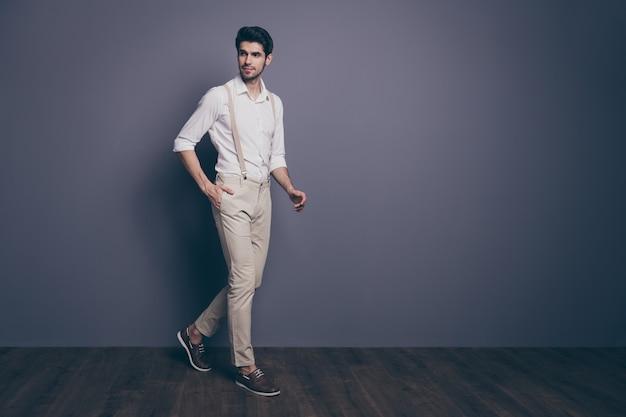 Pełen profil ciała portret atrakcyjnego faceta spacer idź kopia miejsce włóż ręce kieszeń gapią się dobrze wyglądający strój.