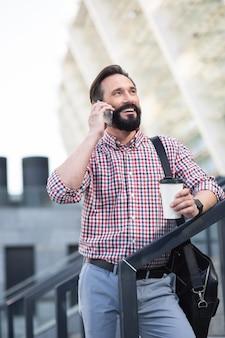 Pełen radości. wesoły przyjemny człowiek stojący na zewnątrz podczas rozmowy telefonicznej