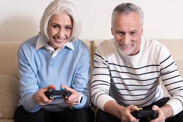 Pełen radości. zachwycona, uśmiechnięta para w wieku trzymająca konsole do gier siedząca na sofie i wyrażająca szczęście