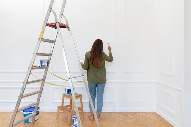 Pełen strzał kobieta malująca ścianę
