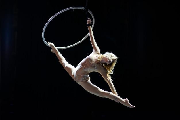 Pełen wdzięku antena akrobata kobieta robi jej występ z obręczą na czarnym tle