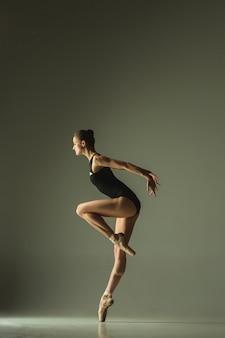 Pełen wdzięku baletnica lub klasyczny taniec baleriny na białym tle na szarym tle studio. okazuje elastyczność i wdzięk. koncepcja tańca, artysty, współczesności, ruchu, akcji i ruchu.