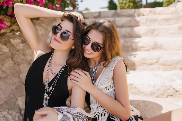 Pełen wdzięku brunetka dziewczyna w okularach przeciwsłonecznych pozowanie z ręką w górze, siedząc obok swojej najlepszej przyjaciółki w vintage dzianinowych ubraniach. portret dwóch wspaniałych sióstr w stylowych dodatkach spędzających razem czas
