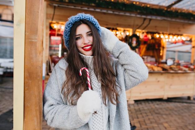 Pełen wdzięku czarnowłosa kobieta z uśmiechem candy cane. zewnątrz portret oszałamiającej modnej dziewczyny w białych rękawiczkach, zabawy na jarmarku bożonarodzeniowym.