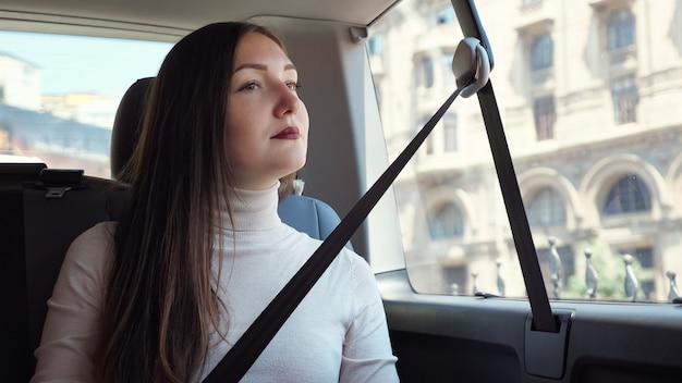 Pełen wdzięku dama z ciemnoczerwonymi ustami siedzi w samochodzie, czekając na kierowcę przed budynkiem architektonicznym na zewnątrz okna zbliżenie