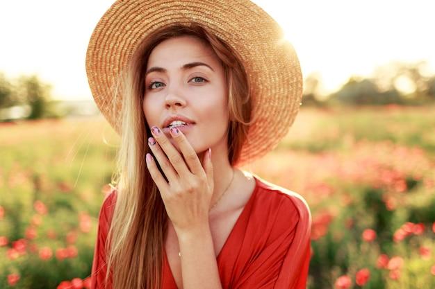 Pełen wdzięku długowłosy kobieta patrząc na horyzont, ciesząc się wolnością. kusząca dziewczyna pozuje w polu maku. ciepłe światło słońca.