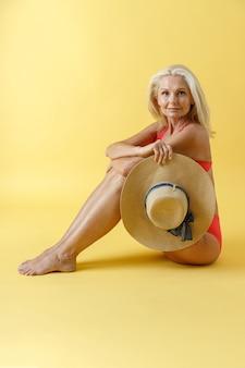 Pełen wdzięku dojrzała blondynka w czerwonym stroju kąpielowym uśmiecha się do kamery trzymając słomkowy kapelusz siedząc na