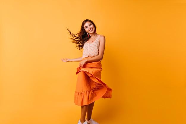 Pełen wdzięku dziewczyna bawi się jej jasną letnią spódnicą. kryty portret zrelaksowanej młodej kobiety tańczącej w studio.