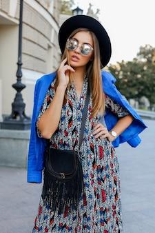 Pełen wdzięku dziewczyna w eleganckim jesiennym stroju spaceru podczas wakacji w europie. stylowa skórzana torba. niebieska kurtka i czarny kapelusz.