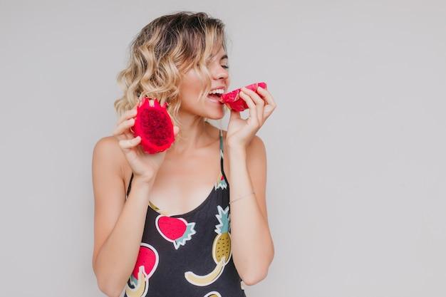 Pełen wdzięku europejska kobieta jedzenie czerwonego pitaya z przyjemnością. elegancka blond modelka korzystających ze smacznych smoczych owoców.