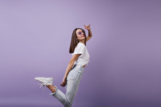 Pełen wdzięku europejska kobieta w modnych trampkach, zabawy. portret całkiem biała dziewczyna w dżinsach na białym tle.