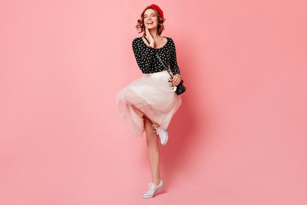 Pełen wdzięku francuska dziewczyna w białych gumowych butach skacze na różowym tle. pełny widok długości emocjonalnej ładnej kobiety w spódnicy tańczy z uśmiechem.