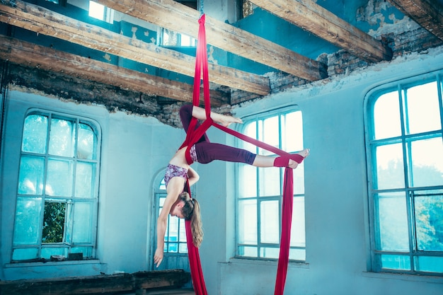 Pełen wdzięku gimnastyczka wykonująca ćwiczenia w powietrzu z czerwonymi tkaninami