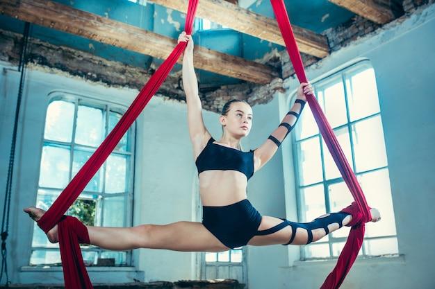 Pełen wdzięku gimnastyczka wykonujący ćwiczenia lotnicze z czerwonymi tkaninami na niebieskim starym poddaszu