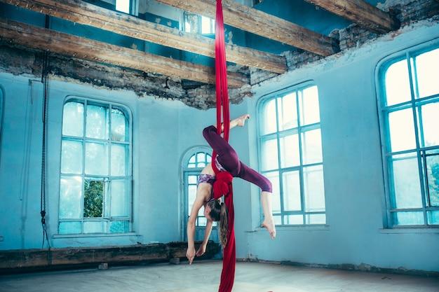 Pełen wdzięku gimnastyczka wykonujący ćwiczenia lotnicze z czerwonymi tkaninami na niebieskim tle starego poddasza. młoda nastolatka kaukaski sprawny. cyrk, akrobatyka, akrobata, wykonawca, sport, fitness, koncepcja gimnastyki