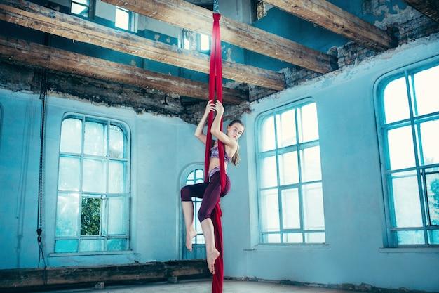 Pełen wdzięku gimnastyczka wykonujący ćwiczenia lotnicze z czerwonymi tkaninami na niebieskim tle starego poddasza.