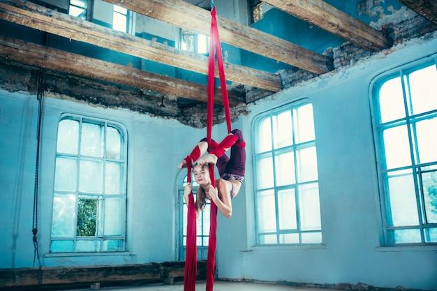 Pełen wdzięku gimnastyk wykonuje powietrznego ćwiczenie przy loftem