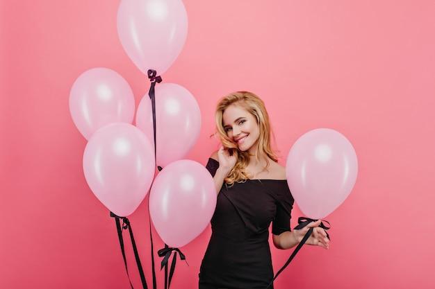 Pełen wdzięku jasnowłosa dziewczyna pozuje z przyjemnością i trzyma balony. wyrafinowana kaukaska dama wyrażająca radość w swoje urodziny.