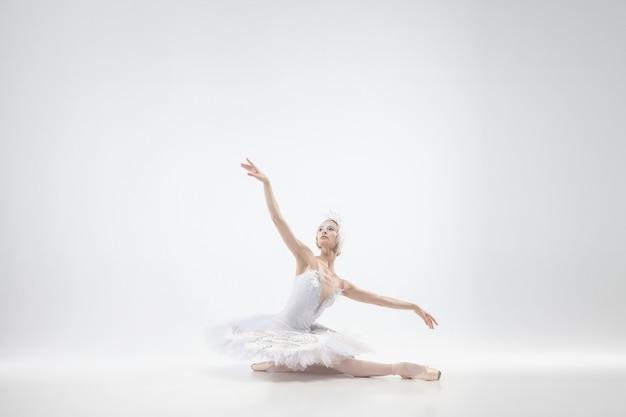 Pełen wdzięku klasyczny taniec baleriny na białym tle na tle białego studia. kobieta w delikatnych ubraniach przypominających białe łabędzie. koncepcja łaski, artysty, ruchu, akcji i ruchu. wygląda nieważko.