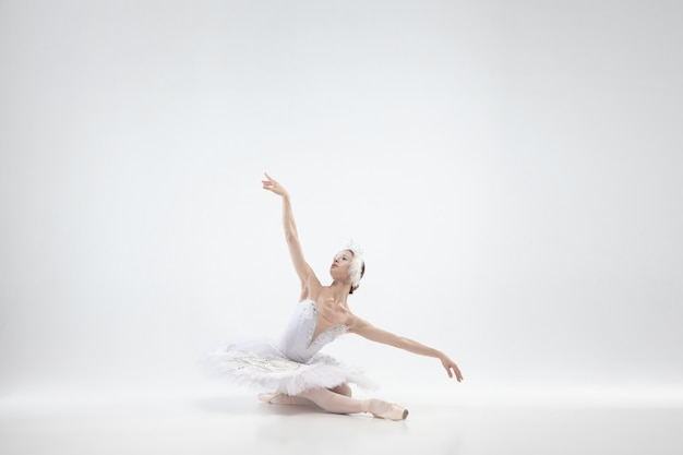 Pełen wdzięku klasyczny taniec baleriny na białym tle.