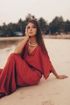 Pełen wdzięku kobieta pozuje na plaży, siedzi na piasku w czerwieni sukni