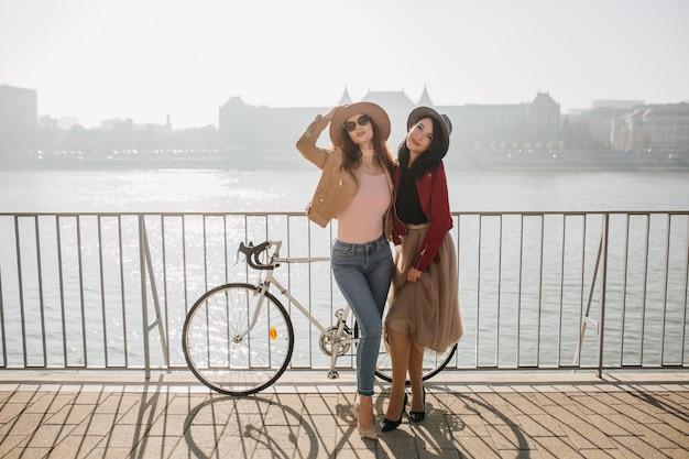 Pełen wdzięku kobieta w dżinsach z siostrą brunetka na nabrzeżu