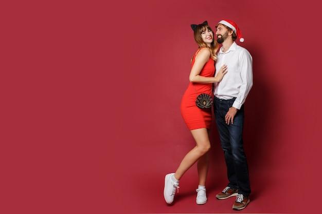 Pełen wdzięku kobieta w kocich uszach maskuje kapelusz i czerwoną krótką sukienkę z chłopakiem pozującym na czerwonym. sylwestrowa impreza. pełna długość .